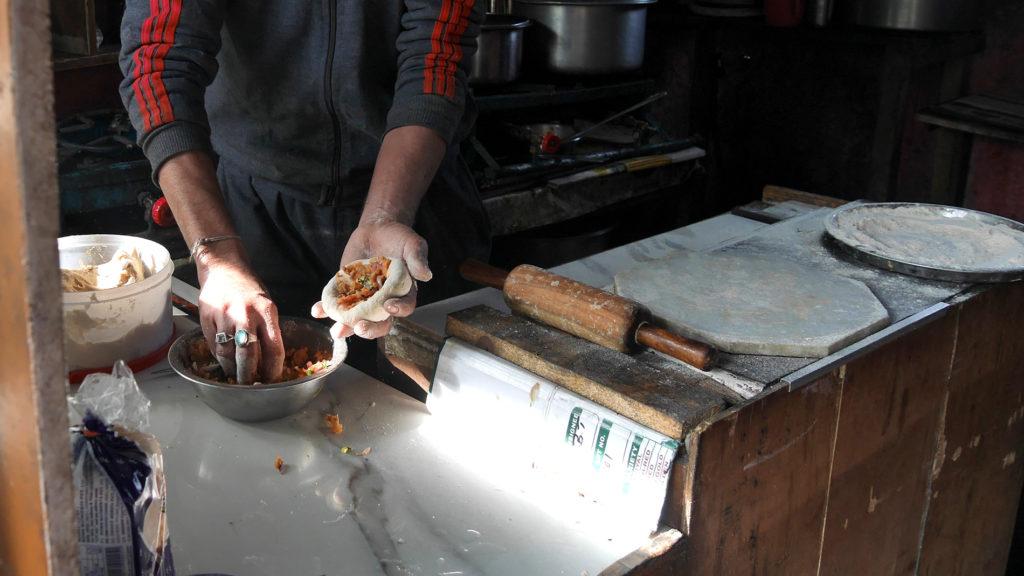 Rana valmistamassa meille peruna-parathaa. Ensin taikina täytetään...
