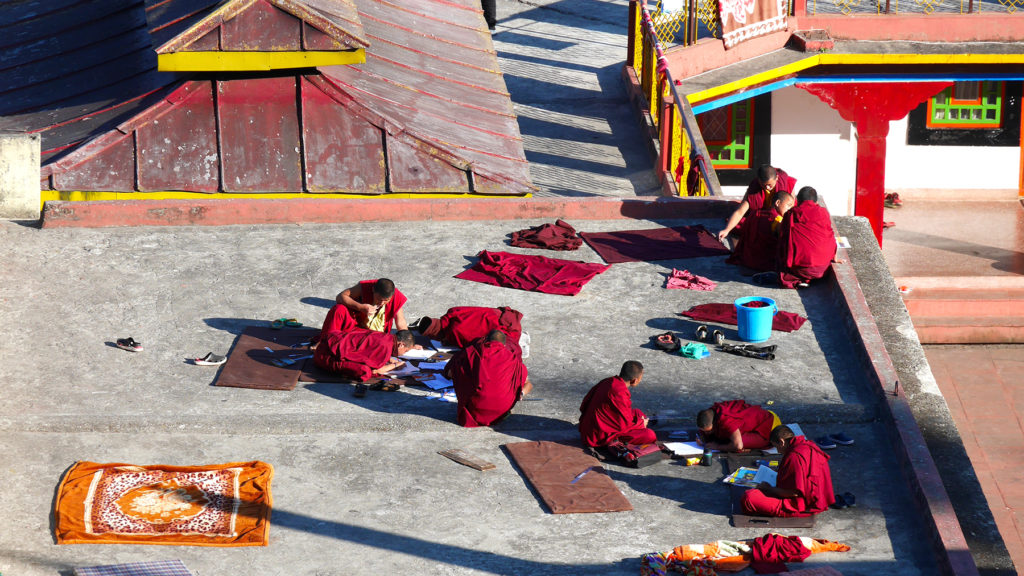 Young monks drawing on the roof