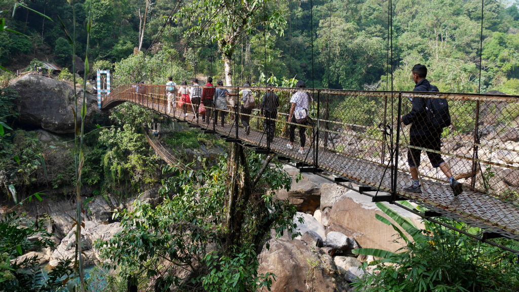 A group of young Indian tourists crossing a bridge just before Nongriat