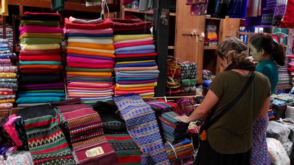 Johanna versucht, die schwierige Auswahl zwischen all den möglichen Farben und Mustern der Longyi-Stoffe zu treffen